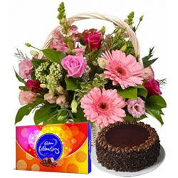 Midnight Delivery of Seasonal Flowers in a Basket with  Chocolate Cake and Cadbury Celebration Pack